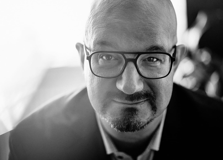 Schwarzweiss Businessportraits eines  leitenden Angestellten  vor natürlichem Hintergrund. Manager mit Bart und Brille