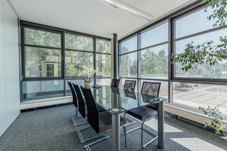 Interiorfotografie eines Besprechnungsraums für ein Unternehmen. 6 Stühlen an einem gläsernen Besprechungstisch. Im Hintegrund eine Glasfront mit Blick ins Grüne.