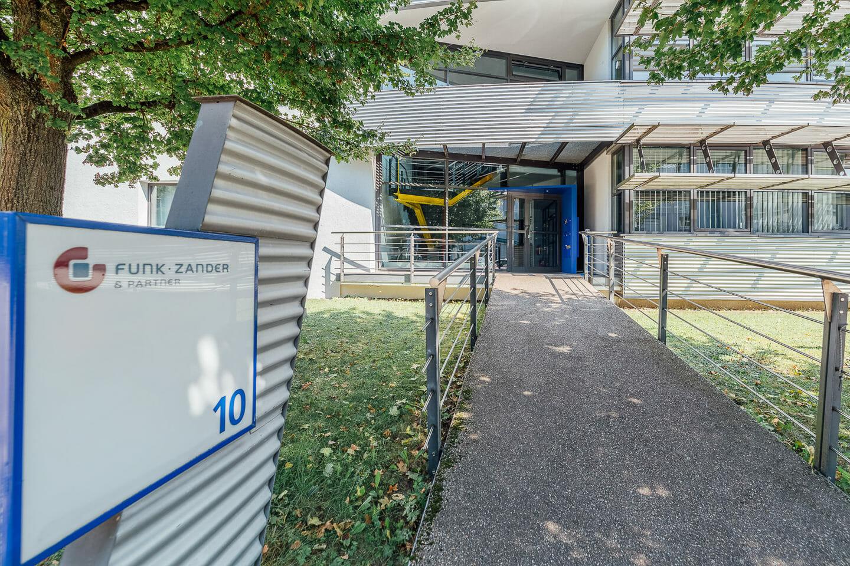 Außenaufnahmen des Eingangsbereichs eines Unternehmessitz. Im Hintergrund ist das Gebäude zu sehen im Vordergrund ein Schild mit dem Namen des Unternehmens