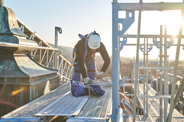 Industriefotografie eines Bauarbeiters auf einem Dach im Gegenlicht