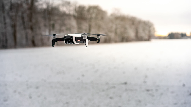 DJI Drohne im Schwebeflug vor verschneiten Hintergrund Professionelle Drohne für Drohnenfotos und Drohnenfilm