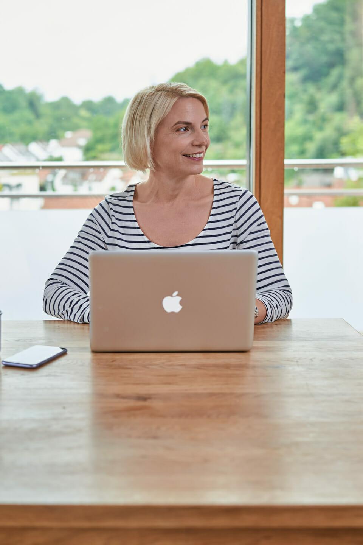 coach sitzt an holztisch vor fenster an laptop businessfoto einer einzelunternehmerin