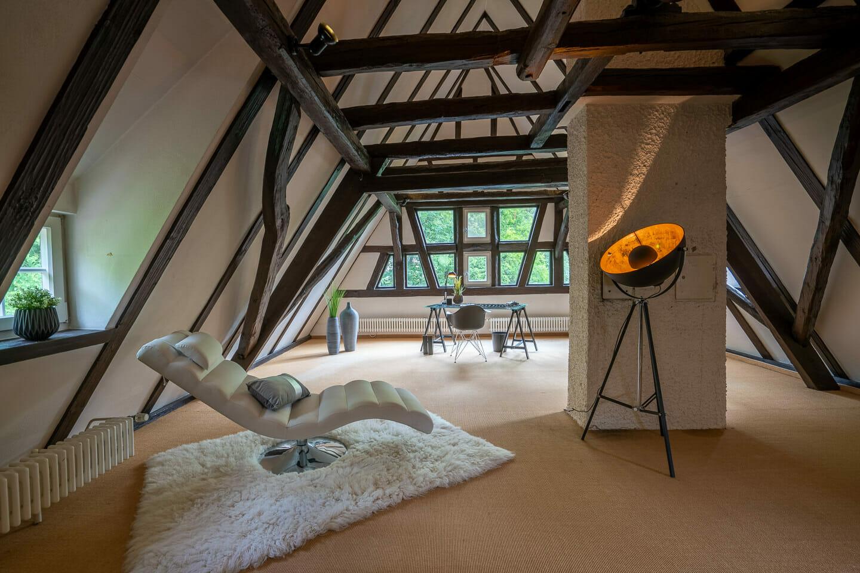 Interiorfotografie eines ausgebauten dachstuhls mit offenem fachwerk in einer luxusimmobilie