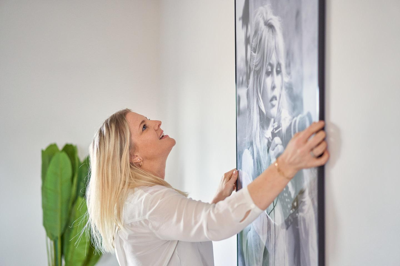 Businessportrait Homestaging Imagefotografie Homestagerin haengt Bild auf