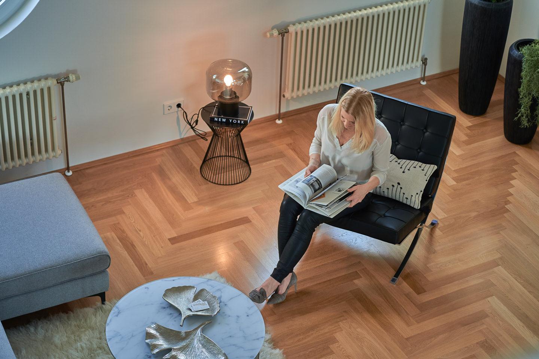 Businessportrait Homestaging Imagefotografie Homestagerin sitzend auf Sessel lesend von Empore aus